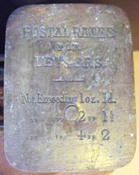 Postal charges (for 1880) are embossed on the scale pan