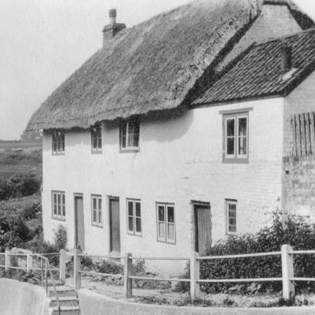 This property still stands, but is now one house and no longer thatched