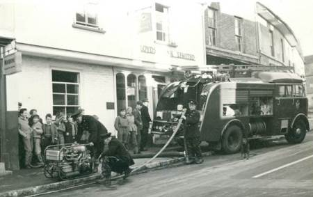 The fire brigade pump out a flooded cellar on High Street, Market Lavington in 1961