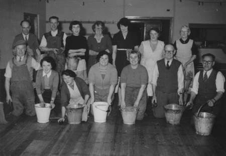 Volunteers scrub the floor at Easterton Village Hall