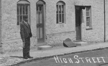 Number 49 High Street with a man posing for the camera